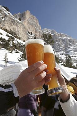 Two persons clinking wheat beer glasses, Alta Badia, Dolomites, Trentino-Alto Adige/Suedtirol, Italy