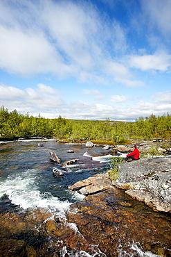 Hiker at Lakktajakko river, Lapland, northern Sweden, Sweden