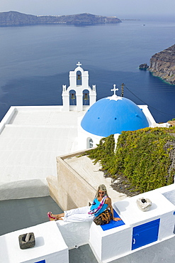 Woman relaxing on a wall above the Greek Orthodox church with a blue dome, Fira, Santorini, Greece, Europe