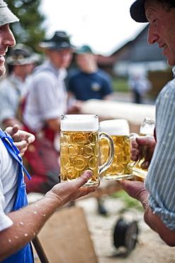 Two men holding beer mugs, Erection of Maypole, Sindelsdorf, Weilheim-Schongau, Bavarian Oberland, Upper Bavaria, Bavaria, Germany