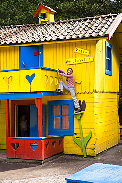 Girl climbing on Pippi Longstocking house, Astrid Lindgren Vaerld, Astrid Lindgren World, Vimmerby, Smaland, South Sweden, Europe