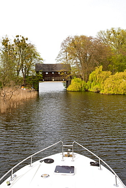 Bow of the houseboat navigating under a roofed bridge near Ahrensberg, Mecklenburgian Lake District, Mecklenburg-Pomerania, Germany