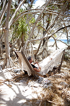 Guest in the hammock right at the beach under Pandanus trees, Wilson Island Resort, Wilson Island, part of the Capricornia Cays National Park, Great Barrier Reef Marine Park, UNESCO World Heritage Site, Queensland, Australia
