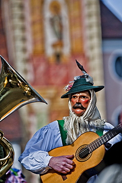 Disguised person playing the guitar at carnival, Mittenwald, Bavaria, Germany, Europe