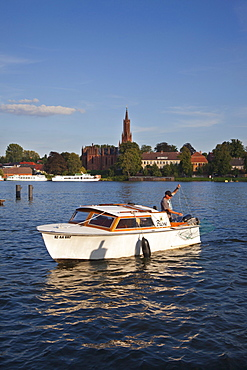 Fisherman in motorboat, view over Fleesensee lake to Malchow monastery, Mueritz-Elde-canal, Mecklenburg lake district, Mecklenburg Western-Pomerania, Germany, Europe