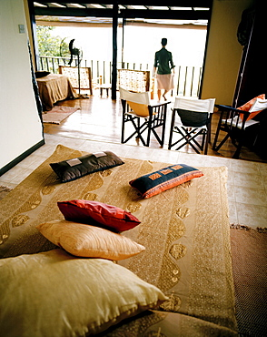 Woman in Superior Room Chalet, Mango Lodge, view over Anse Volbert, Bahia Ste. Anne, Praslin, Republic of Seychelles, Indian Ocean