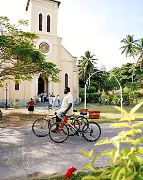 Man with rental bikes passing in front of the church at La Passe, La Digue, La Digue and Inner Islands, Republic of Seychelles, Indian Ocean