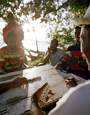 Men playing domino on the beach in the evening, La Passe, La Digue, La Digue and Inner Islands, Republic of Seychelles, Indian Ocean