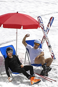 Two skiers in deck chairs in the snow, Alto Adige, South Tyrol, Italy, Europe