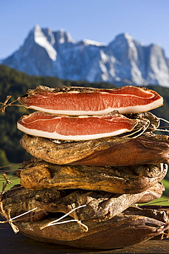 A pile of smoked bacon in front of Schlern mountain range, Kastelruth, Alto Adige, South Tyrol, Italy, Europe