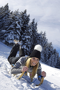 Young woman with sledge in snowy landscape, Alto Adige, South Tyrol, Italy, Europe