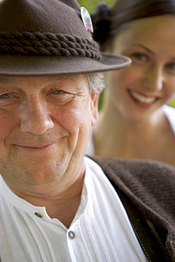 Mature man with young woman in background in beergarden, Bavaria, Germany