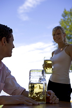 Two young adults meet in beergarden near Lake Starnberg, Bavaria, Germany