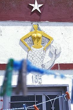 Figure of a mermaid above a door, Ilha da Culatra, Parque Natural da Ria Formosa, Algarve, Portugal, Europe