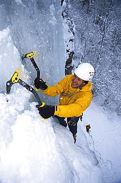Man climbing up ice fall, Unterlaussa, Upper Austria, Austria