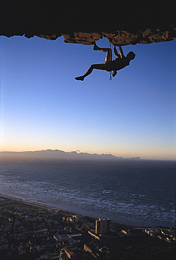 Rock climber climbing an overhang, Muizenberg Bay, South Africa