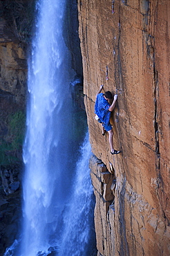 Man climbing a steep rock face near a waterfall, Waterval Boven, South Africa