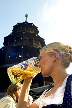 Girl in Dirndl dress drinking beer in beergarden, Chinesischer Turm, English Garden, Munich, Bavaria, Germany