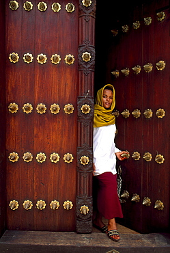 African woman going through a door, Zanzibar, Tansania, Africa