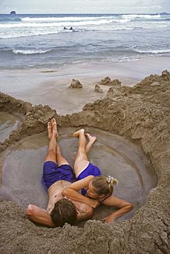Young couple bathing in hot water on the beach, Coromandel Peninsula, North Island, Oceania