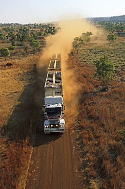 aerial view of livestock truck, triple-trailer driving on dirt road, Kimberley, Western Australia