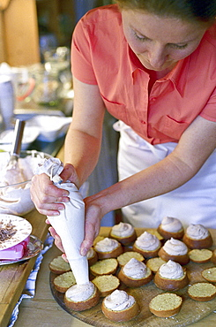 A woman filling muffins at a bakery