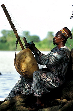 Man playing a harp by the Gambia river, Gambia, Africa