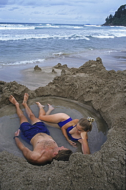 Young couple bathing in hot water on the beach, Coromandel Peninsula, North Island, Oceania