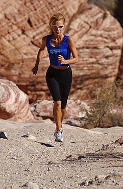 Woman jogging, running in Joshua Tree National Park, California, USA