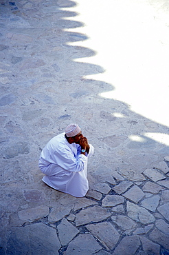 A man cowering in the shadow, Nizwa, Oman