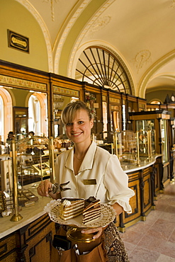 Waitress serving cake in Cafe Gerbeaud, Waitress serving fancy cake in Cafe Gerbeaud, which is specialized in hungarian cakes, Pest, Budapest, Hungary