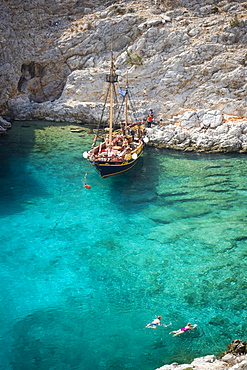 People swimming in a bay of Kalymnos next to a sailing boat, Greece