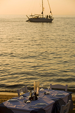 View over a table with glasses and plates to a sailingboat on the sea, Little Venice, Mykonos-Town, Mykonos, Greece