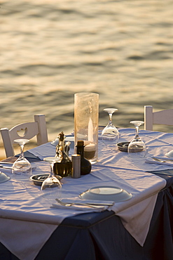 Table with glasses and plates at bank, Little Venice, Mykonos-Town, Mykonos, Greece