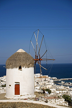 View from hill with famous traditional windmill over the town to the sea with ships, Mykonos-Town, Mykonos, Greece