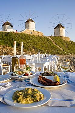 Different greek starters served in the Sea Satin Market Restaurant, windmills in background, Mykonos-Town, Mykonos, Greece