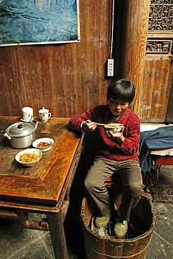 A boy eating and warming his feet at a foot warmer, Hongcun, Huang Shan, China, Asia