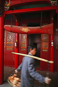 Porter with building material and wooden fish in front of Qiyuan monastery, Jiuhuashan, Anhui province, China, Asia
