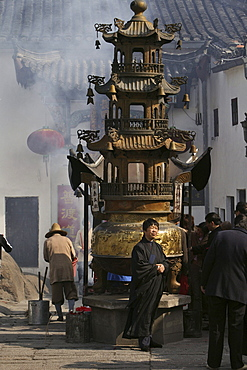 People standing at incense pagoda in front of Longevity monastery, Jiuhua Shan, Anhui province, China, Asia