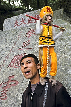 Man with performing monkey, Monkey is dressed up as the monkey king Sun Wukong, Mount Tai, Tai Shan, Shandong province, World Heritage, UNESCO, China
