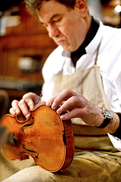 Man reparing a violin, Antique Violin repair shop, Old Town, Prague, Czech Republic