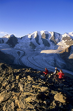 Three mountaineerers descending from summit of Munt Pers with view to Piz Palue and glacier of Pers, Pontresina, St. Moritz, Bernina, Oberengadin, Grisons, Switzerland