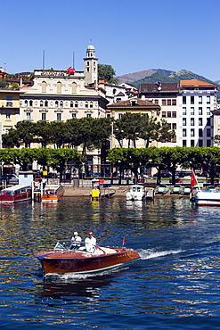 View over Lake Lugano to Luganow with cathedral St. Lorenzo, small motorboat in foreground, Lugano, Ticino, Switzerland