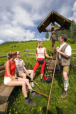 Three hikers resting at a crucifix and talking to a native man, Grossarl Valley, Salzburg, Austria