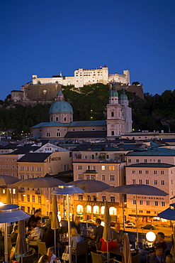 View over illuminated roof deck of restaurant Hotel Stein to old town with Salzburg Cathedral and Hohensalzburg Fortress, largest, fully-preserved fortress in central Europe, in the evening, Salzburg, Salzburg, Austria, Since 1996 historic centre of the city part of the UNESCO World Heritage Site