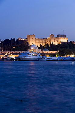 Ships and boats anchoring in Mandraki harbour (translated literally: fold) in the evening, illuminated Palace of the Grand Master and Nea Agora in background, Rhodes Town, Rhodes, Greece