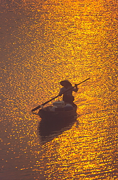 Vietnam, Nha Thrang, river dalta at sunset, woman on a fisherboat