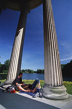 Couple having a rest at the Apollo Temple, Nymphenburg, Munich, Bavaria, Germany