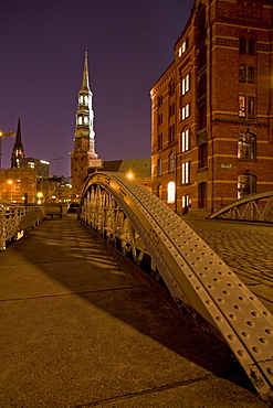 View over bridge to St. Catherine's Church and St. Nikolai's Church at night, Speicherstadt, Hamburg, Germany