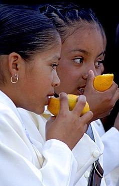 Two children eating oranges, San Miguel de Allende, Mexico